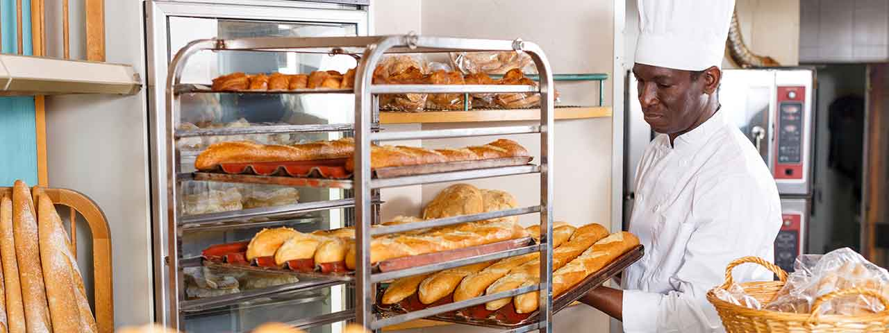 A master baker pulls loaves from an oven in his bakery.