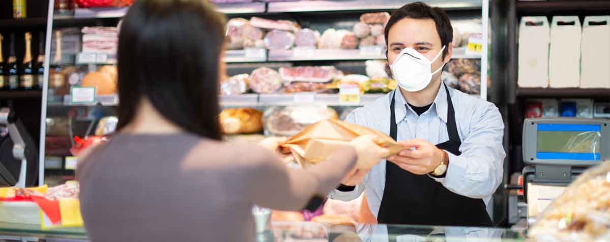A retailer hands a package to a customer, both wearing face masks and proper social distancing.
