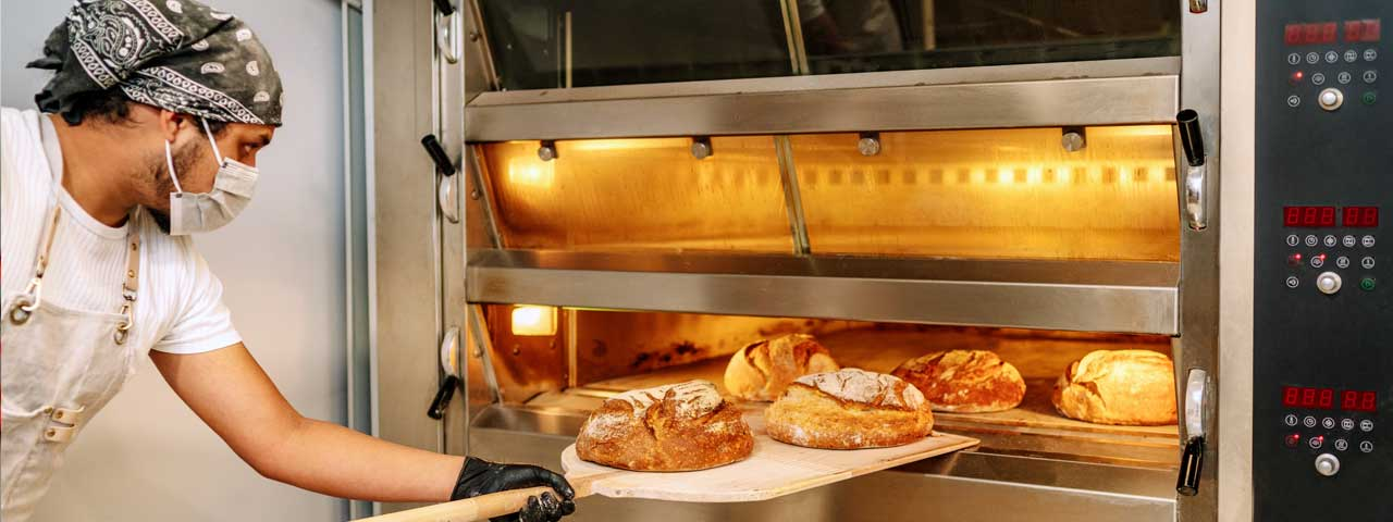 A baker removes fresh bread from the oven.
