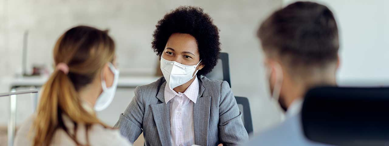 Una mujer que lleva una máscara aconseja a los empresarios sobre las opciones de aplicación.