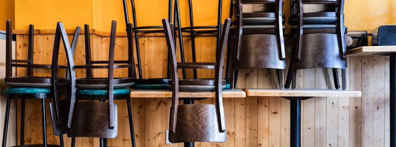 Le sedie sono impilate sui tavoli in un ristorante chiuso.