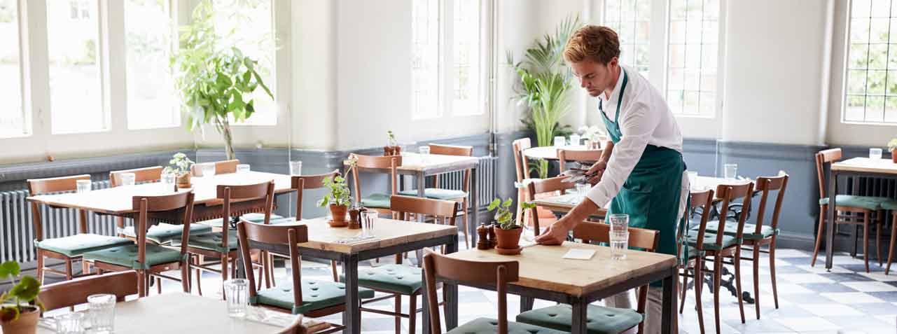บริกรจัดโต๊ะในร้านอาหารที่ว่างเปล่า